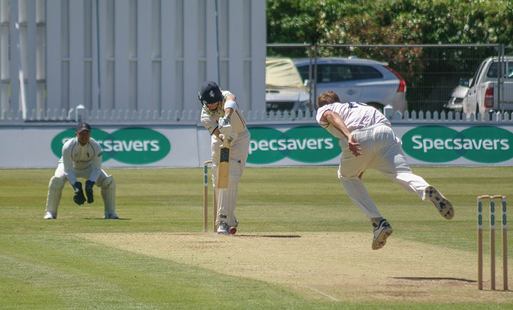 bowler runs in and bowls toward as a batsman in a cricket match